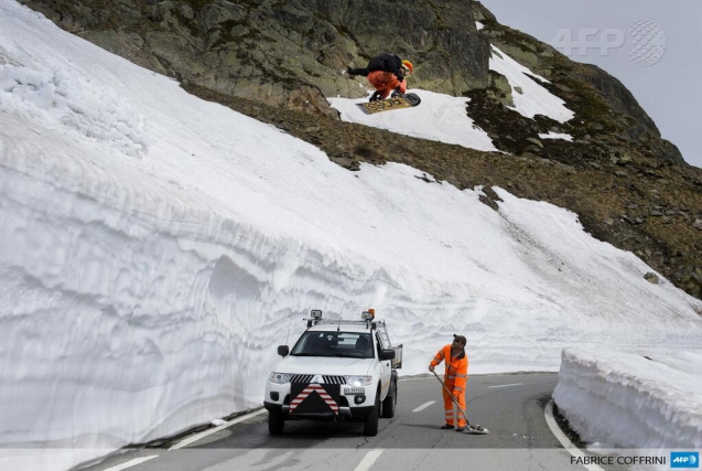 The official news agency Agence France-Presse (@AFP) tweeted this photo today of a snowboarder jumping across a mountain pass connecting Switzerland and Italy as a worker clears snow. Taken June 12 (yesterday).