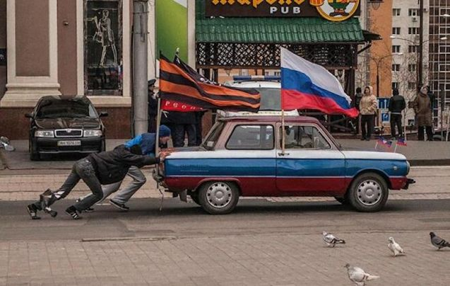 Ukraine: pro-Russia supporters push their ZAZ Zaporozhets through the streets of Donetsk. There was a plan last week to hold a referendum in the south east industrial city, about 50 miles from the Russian border, about joining the UK. Donetsk was founded in 1869 by John Hughes, a Welsh businessman. Photo by Андрей Шокотко, Andrew Shokotko.