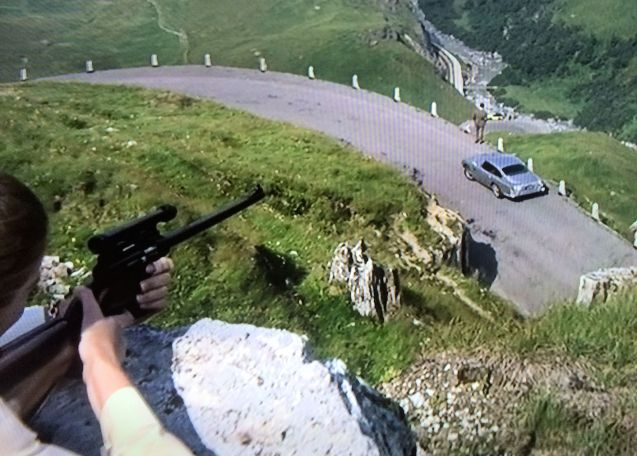 In the book, Bonds tails Goldfinger across France to Coppet, just up the lake from Geneva. In the film, the action takes place on the Furka Pass. Whatever other liberties it takes with Fleming's original, the movie's basic sequence is correct – the first shot of Goldfinger's Rolls-Royce is heading up the mountain from the Belvedere Hotel on the west ascent (i.e. in the opposite to us). Bond and Tilly Masterson follow Goldfinger over the pass until he stops to buy apples from a stall on the final hairpin, just above the Reuss River before Realp. As Bond watches over from higher up the mountain, Masterson, higher still, takes her famous shot, kicking up the dust beside Bond's foot. Bond then shreds Tilly's tyres on the H19 between Realp and Hospental, beside the Furka railway line, and drops her at the Aurora filling station on Gotthardstrasse on the way into Andermatt (now the Aurora Garage and Hotel, and restaurant Aelpli).
