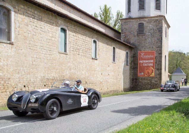 32: Dominique Jouvin and Claudine Jouvin in a Jaguar XK 120 Roadster pulling in to the Abbaye de l'Escaladieu. Photo Departement des Hautes-Pyrenees