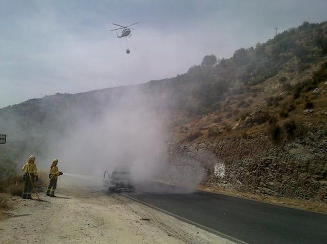 A helicopter drops water on a burning car at Carataunas in the Sierra Nevada near Granada, southern Spain, to prevent the fire spreading to nearby forest. Photo via @Plan_INFOCA