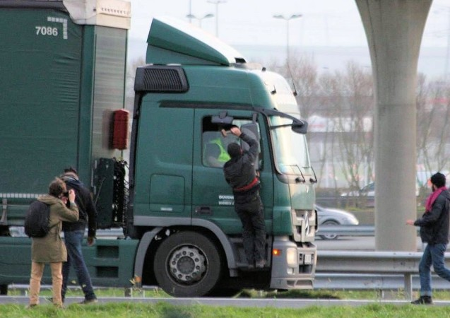A migrant threatens a truck driver with a lump hammer in Calais in December. A shocking reminder, as strike action is threatened again, that none of the issues which caused such problems in the summer are done and dusted just yet. Photo via Les Calaisiens en Colere/Facebook.